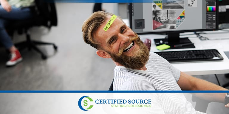 Picture of man with sticky note that says Be Happy on forehead