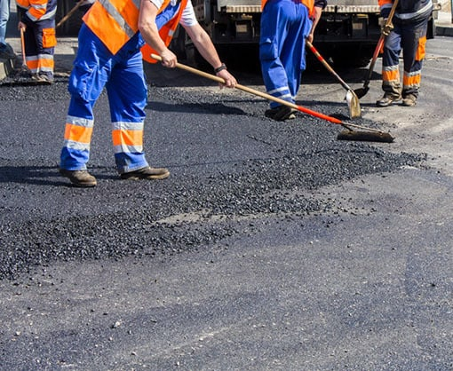 Industrial worker spreading asphalt