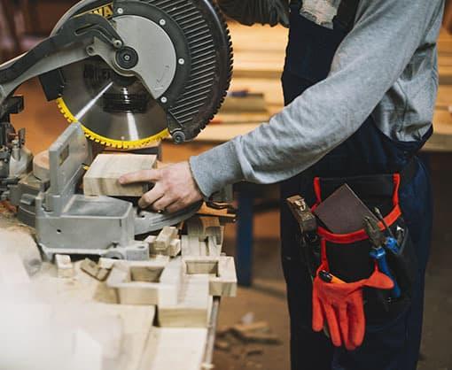 Carpenter cutting wood using a machine