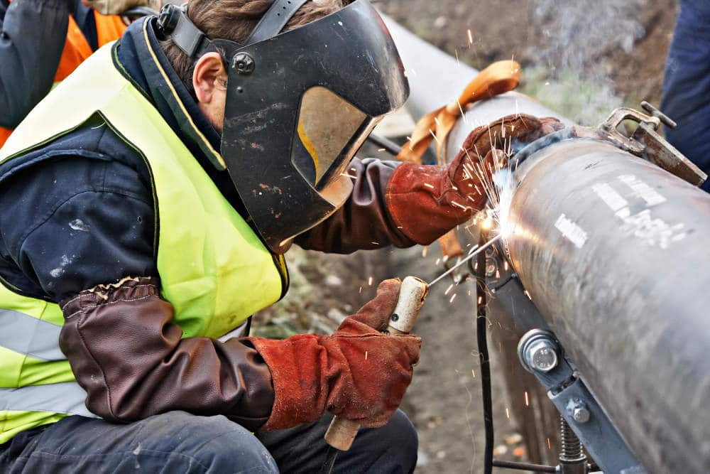 Industrial welder doing work on a metal pipe