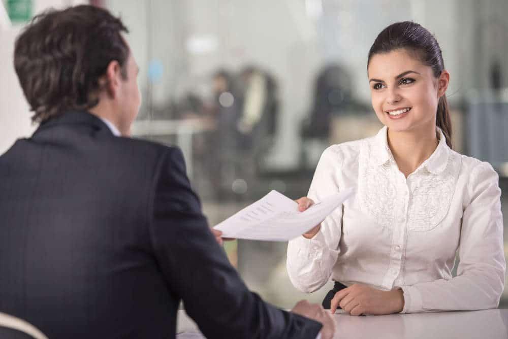 Professionally dressed woman handing resume to professionally dressed man