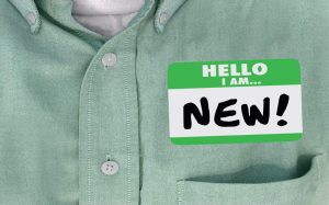 person wearing name tag that says Hello I am New!