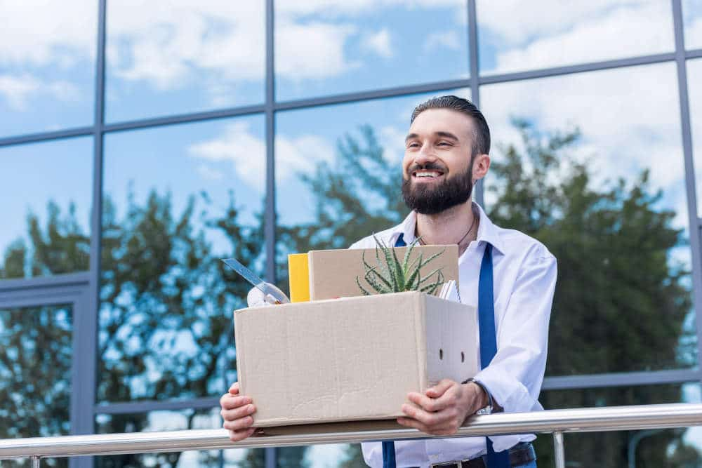 Smiling man holding box with personal items