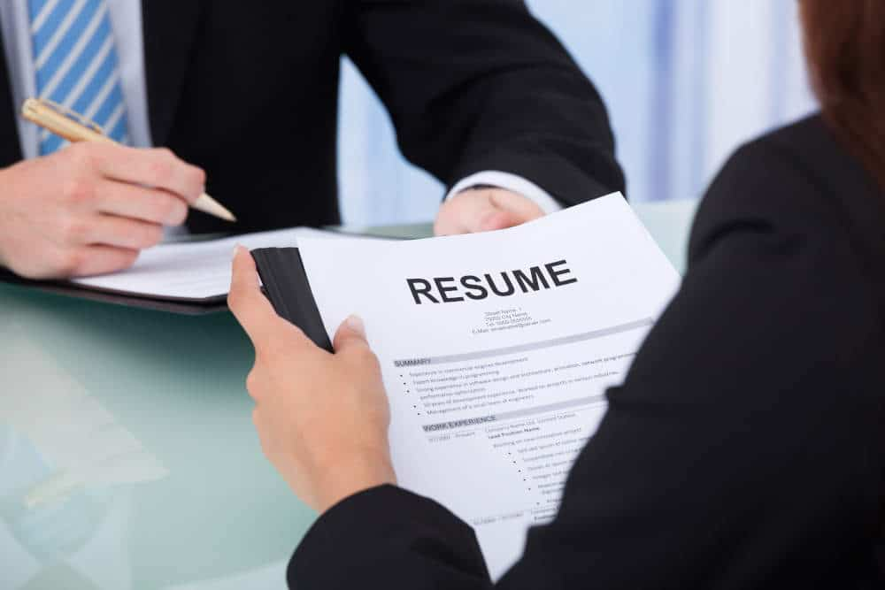 person holding resume in front of interviewer