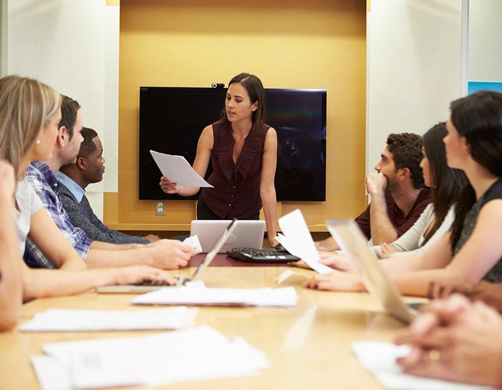 Female Boss Addressing Meeting Around Boardroom Table